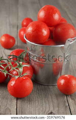 Whole wet tomatoes in galvanized bucket on rustic wooden table.
