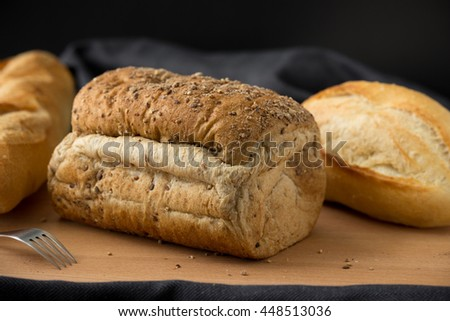 Whole wheat bread and French baguette, food background - stock photo