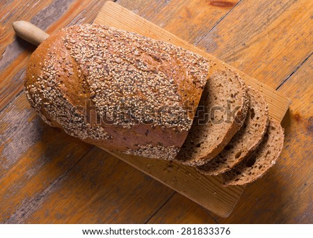 Whole wheat bread with seeds on a cutting board. - stock photo