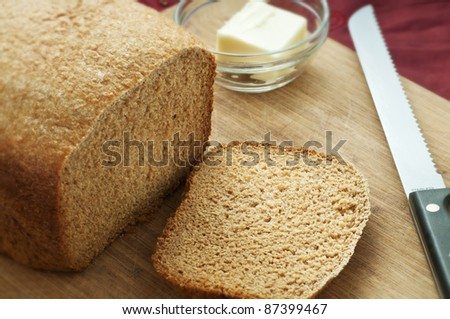 Whole wheat loaf of bread sliced with ramekin of butter - stock photo