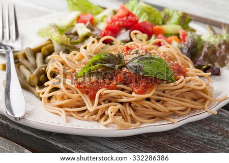 whole wheat spaghetti topped with organic homemade marinara sauce served with green beans and an Italian side salad macro shot