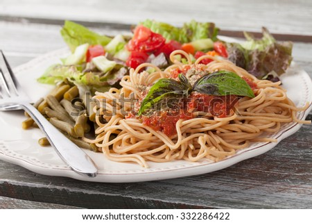 whole wheat spaghetti topped with organic homemade marinara sauce served with green beans and an Italian side salad side view