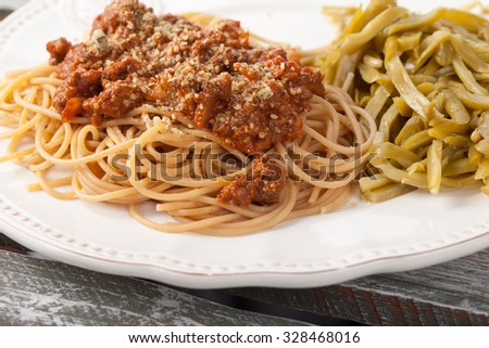 Whole wheat spaghetti with French style cut green beans on a weathered barn wood table - stock photo