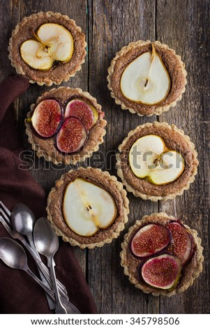 whole wheat tarts  with chocolate frangipane, figs, apple and pears on wooden background, top view - stock photo