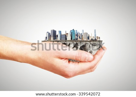 Whole world in one hand concept with man hand and part of megapolis city district - stock photo