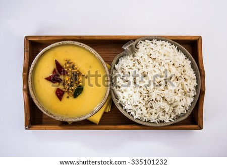 Whole Yellow Lentil with Rice, dal tadka and jeera rice, Indian Dish, cooked rice and cooked Arhar or Toor dal (Pigeon Pea), served in ceramic bowl in a tray, isolated, top view on white background  - stock photo