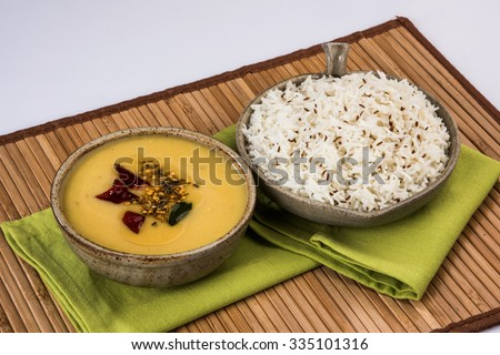 Whole Yellow Lentil with Rice, dal tadka and jeera rice, Indian Dish, cooked rice and cooked Arhar or Toor dal (Pigeon Pea), served in ceramic bowl in a tray, isolated, front view on wooden mat  - stock photo