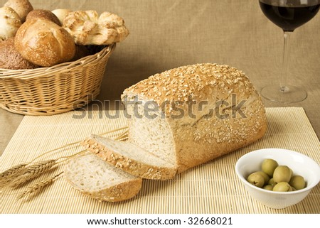 Wholegrain bread loaf with a cup of wine and some olives - stock photo