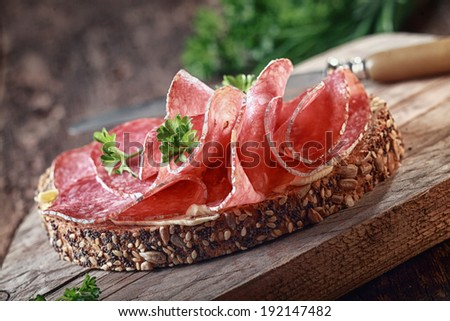 Wholegrain bread with seeds topped with spicy Italian salami sausage and parsley on an old grunge rustic wooden board - stock photo
