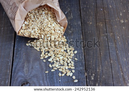 Wholegrain oat flakes in a paper bag - stock photo