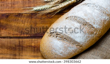 wholemeal bread and wheat spike on wooden dark background