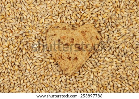 Wholemeal bread in the shape of a heart surrounded by barley grains - stock photo