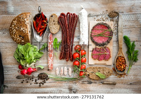 Wholemeal bread with dried salami  and vegetables on a wooden rustic table - stock photo