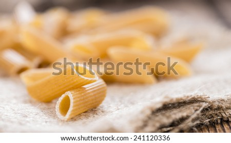 Wholemeal Pasta (Penne) as close-up shot on vintage wooden background - stock photo