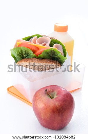 Wholemeal sandwich with fresh vegetables and ham with apple in a lunchbox - stock photo