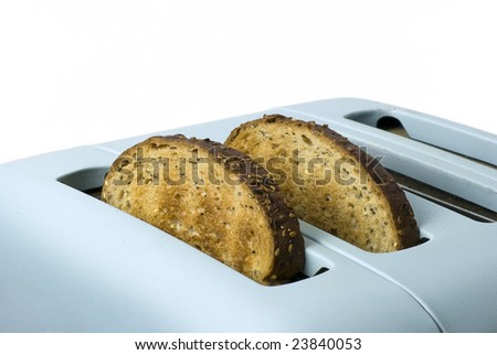 wholemeal toast popping out of toaster; isolated against white ground - stock photo