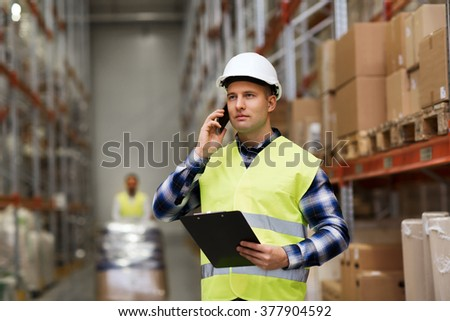 wholesale, logistic, business, export and people concept - man in hardhat and reflective safety vest with clipboard calling on smartphone at warehouse - stock photo