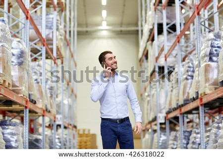 wholesale, logistic, business, export and people concept - smiling businessman calling on smartphone at warehouse - stock photo