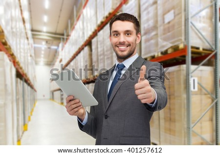 wholesale, logistic business, export, technology and people concept - smiling businessman with tablet pc computer showing thumbs up over warehouse background - stock photo