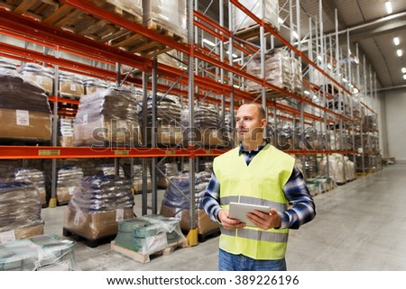 wholesale, logistic, technology, shipment and people concept - man or manual worker with tablet pc at warehouse - stock photo