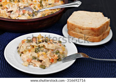 Wholesome casserole of chicken, vegetables and noodles in a stoneware dish.  One serving with a side of bread.