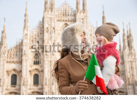 Why not to hang out in Italian fashion capital Milan on winter holidays with family. Smiling mother and daughter holding Italian flag in front of Duomo