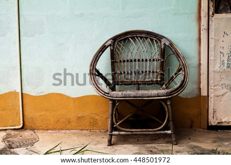 Wicker armchair with old wall background