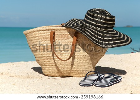 wicker bag hat and flip flops on the beach - stock photo