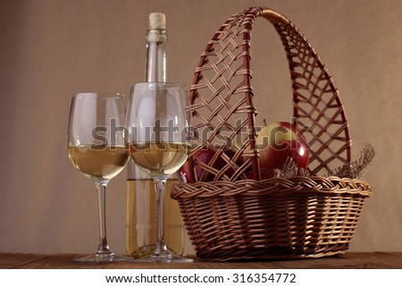 Wicker basket covered with burlap complete fresh ripe red apples two half filled glasses with white sweet wine opened unfull transparent bottle on wooden table, horizontal photo - stock photo
