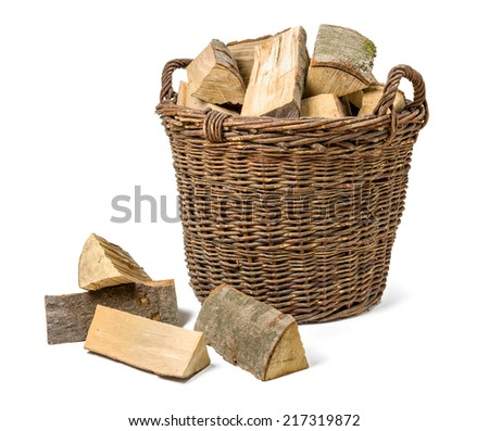 Wicker basket filled with firewood - stock photo
