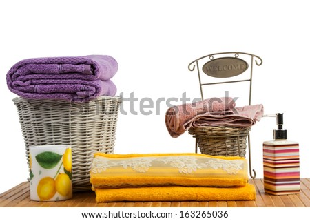 Wicker basket full of clean colored towels on a wooden table in a bathroom set - stock photo