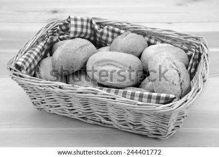 Wicker basket full of crusty bread rolls on a wooden table - monochrome processing - stock photo