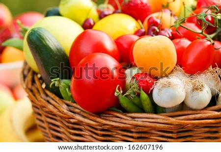 Wicker basket full of organic fruit and vegetables - stock photo