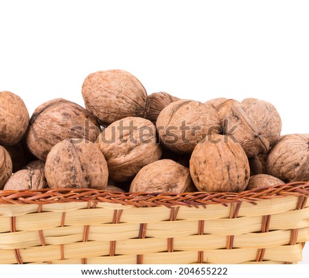 Wicker basket full of walnuts. Isolated on a white background.