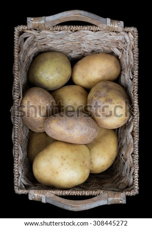 Wicker basket isolated on a black background, holding many fresh, ripe potatoes. - stock photo