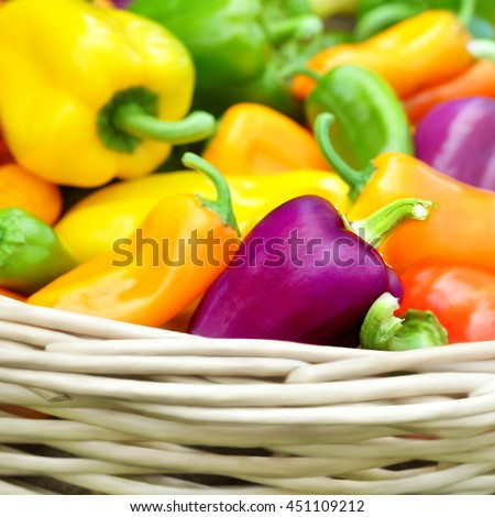 Wicker basket of colorful fresh harvested bell peppers, selective focus - stock photo