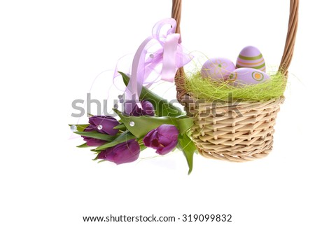 wicker basket of easter eggs with purple tulips - stock photo