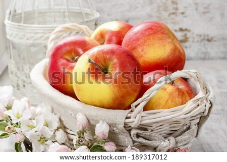 Wicker basket of fresh red ripe apples. - stock photo