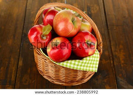 Wicker basket of red apples with green napkin on wooden background - stock photo