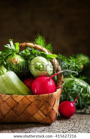 Wicker basket with a crop of spring vegetables and herbs, vintage wooden background, still life in rustic style, selective focus, shallow depth of field