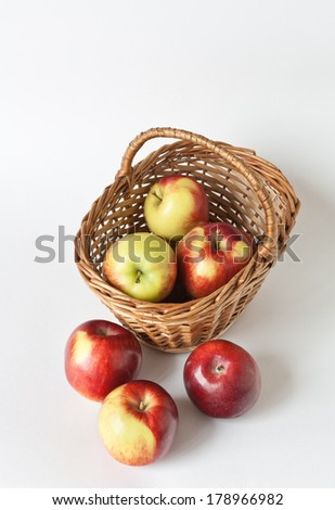 Wicker basket with apples on white background