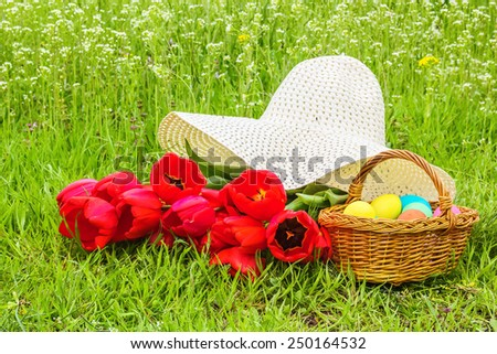 Wicker basket with Easter colored eggs, a bouquet of red tulips and white straw hat on spring flowering meadow - stock photo