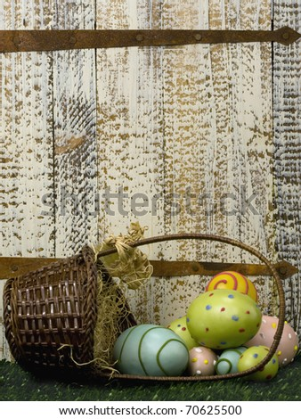 Wicker basket with Easter eggs on grass by old rusted door - stock photo
