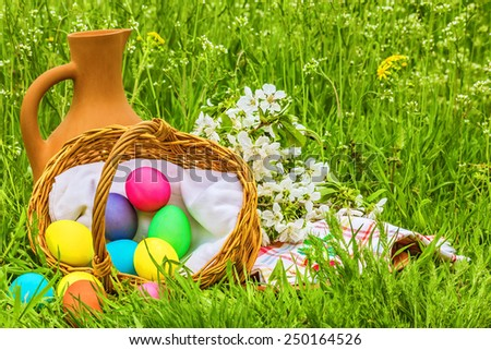 Wicker basket with Easter painted eggs, a clay jug and flowering branch cherry on the spring green meadow - stock photo