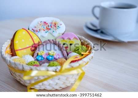 wicker basket with Easter sweets and coffee cup on wooden table