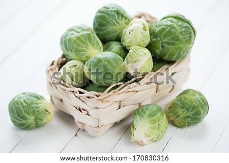 Wicker basket with fresh brussels, white wooden background - stock photo