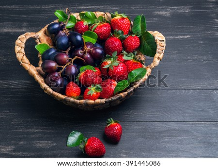 Wicker basket with green leaves of lime, grapes and ripe strawberries on a dark black wooden background, Empty place for text - stock photo