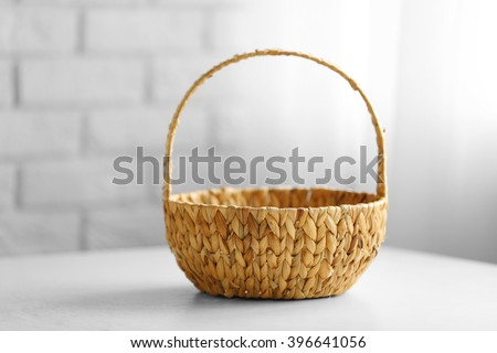 Wicker basket with handle on wooden table, closeup - stock photo