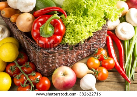 wicker basket with many fruits and vegetables on wooden table top view