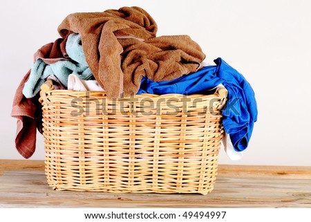 Wicker basket with multi-colored laundry on a weathered wooden plank deck before a white background - stock photo